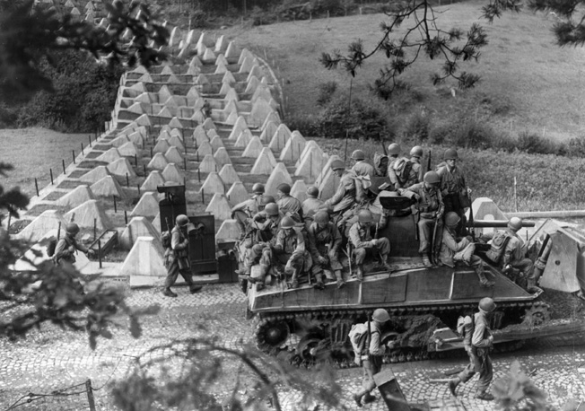 "South of Aachen, American soldiers accompanied by an M-4 Sherman tank advance past ""dragon's teeth"" tank obstacles on the Siegfried Line."