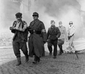 On October 5, 1944, wounded German prisoners are marched westward through the now quiet streets of Aachen.