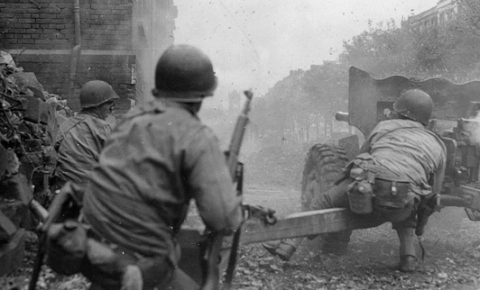 In the close quarters of a rubble-strewn street in Aachen, American soldiers fire a 57mm antitank weapon against a distant German target. Urban warfare became a new concept for Allied armies, and they adapted during the advance into Germany.