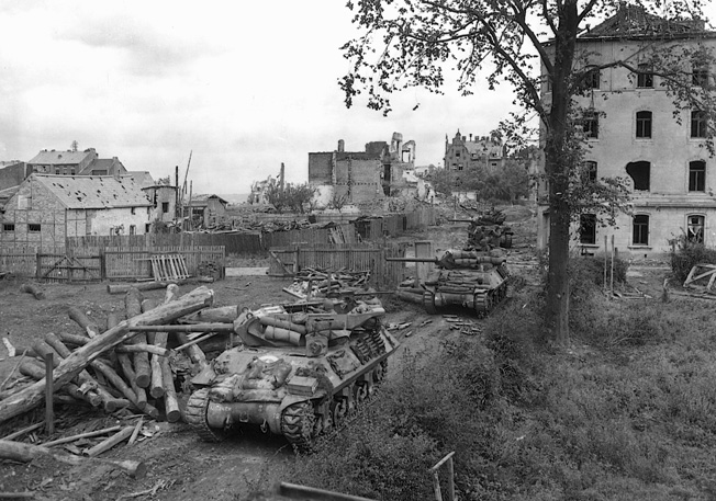 Near Aachen on October 14, 1944, open-turreted American M-10 tank destroyers fire on German observation posts in preparation for an assault and to prevent the ranging of German artillery.