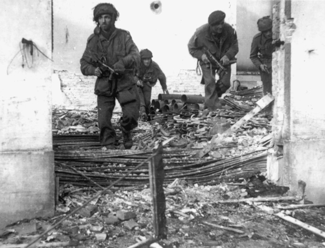 The British patrol through ruined homes in Oosterbeek near Arnhem. By the 25th of September when this picture was taken, the British perimeter was small.