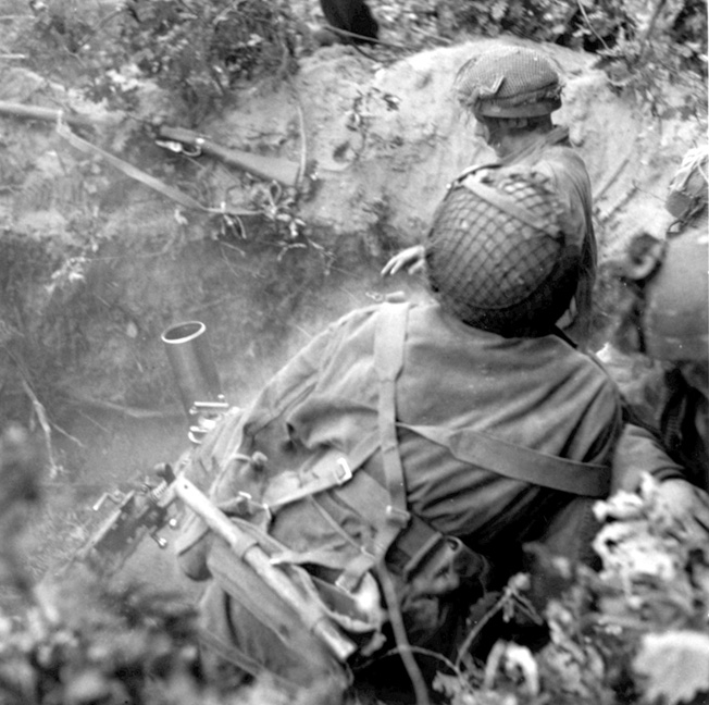 British fighters use a three-inch mortar to fend off Germans.