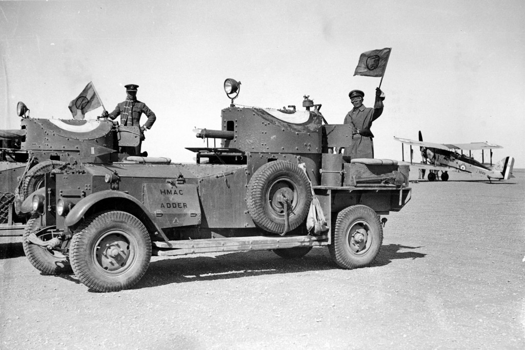 An armored car, vital to the British force crossing the desert. An RAF biplane is at right.
