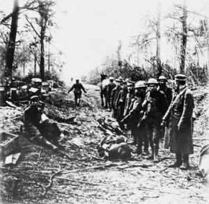 Grim-faced American soldiers guard German prisoners taken at Belleau Wood.
