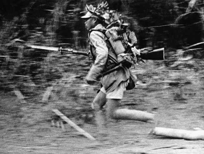 A Japanese soldier wearing camouflage runs through the Burmese jungle during fighting with American troops.