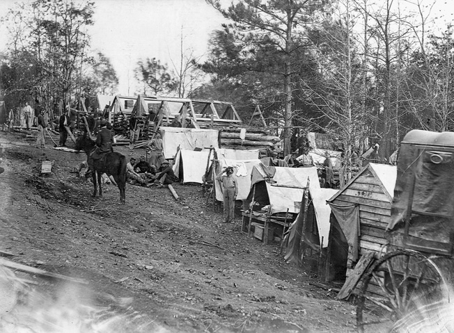 Soldiers construct log huts from nearby trees.