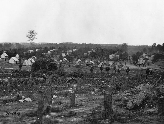 The forests of northern Virginia did not stand a chance against the need of soldiers to build shelters and keep fires burning. Sentries stand guard in front of the rows of tents.