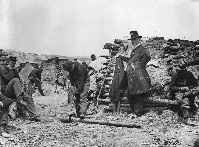 Soldiers chop wood and use mud to build winter quarters. The older soldier, second from the right, is probably an officer, judging for the dress and age.