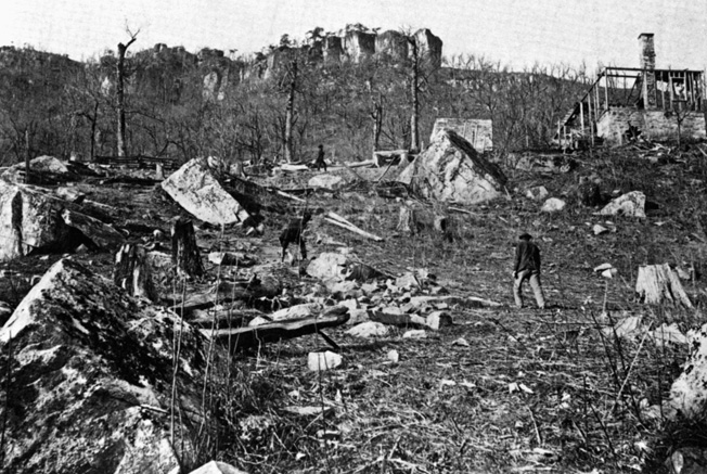 This photograph taken just after the battle shows Union soldiers searching through the grounds at Cravens House for souvenirs. The house itself, at right, shows ravages of the battle.