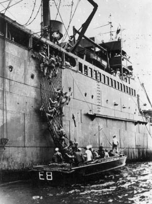 Clambering down the side of their transport vessel, units of the 1st Marine Division and the 1st Infantry Division are preparing to board their landing craft during the 1941 joint amphibious exercises conducted at New River, North Carolina.