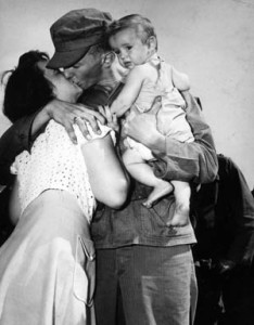 Corporal John W. Simms bids goodbye to his wife and child as he prepares to leave for Korea in 1950.