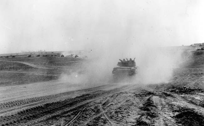 Allied armored advances across Normandy, raising a cloud of dust, as they encircle the Germans near Falaise.