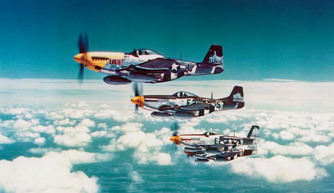 Carrying drop tanks to extend their range, a flight of P-51 Mustangs maintains formation in the skies over Europe.