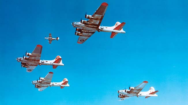 A P-51 Mustang fighter, upper left, flies escort duty with a formation of B-17 Flying Fortress bombers.