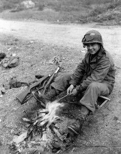 A private with the 42nd Infantry Division cooks a fish over his own personal fire in the Lembach Forest area in France.