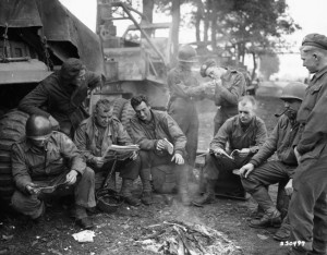 British and American combat engineers swap stories, news, and cigarettes around a small fire as they wait for a call to build a Bailey Bridge near Someren, Holland. The British are with the 15th Scottish Division, while the Americans are with the 7th Armored Division.