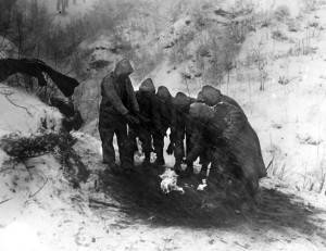 Artillerymen of the 10th Mountain Division huddle around a fire as snow whips around them. Fires were often built on the opposite sides of slopes to hide them from the enemy.