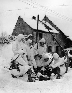 "These soldiers, nicknamed ""Trouble Shooters,"" with the 100th Infantry Division, keep warm over a fire near Butten, France. Two of the soldiers sport M3 Grease Guns."