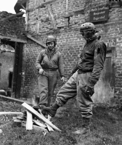 Two tankers with the 2nd Armored Division warm their feet by a fire in Beggendorf, Germany. They had just finished fighting for more than 24 hours without a rest.