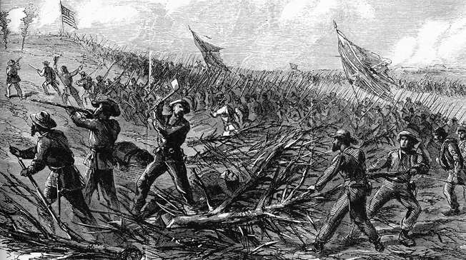 Confederate axemen chop through the barricades surrounding Ft. Stedmen as troops pour through the gaps of the now-breached defenses.