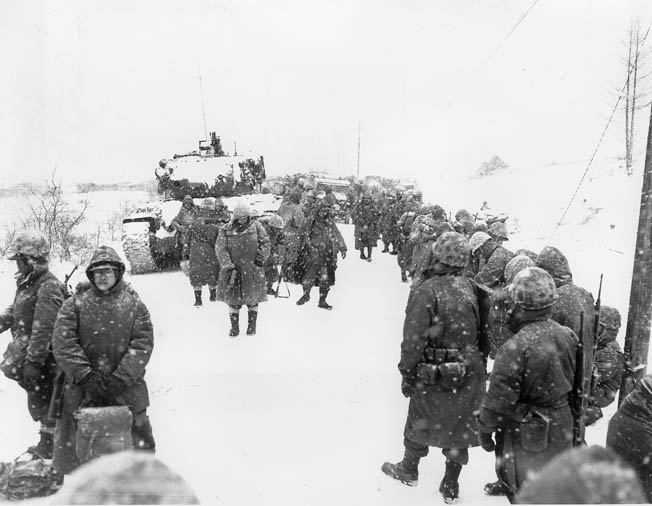 U.S. Marines suffering from exposure to freezing weather retreat from their advanced positions at the Chosin Reservoir.