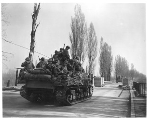 U.S. tanks loaded with infantrymen pass through a final roadblock before crossing the Rhine River.