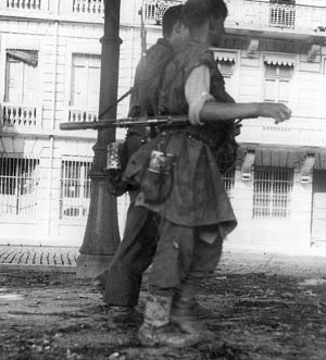During their retreat from Lyon, a pair of German soldiers walk down a desolate city street.