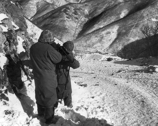 Two Marines line up a light machine gun on a Communist position in late December 1950. The weather was bitter cold.