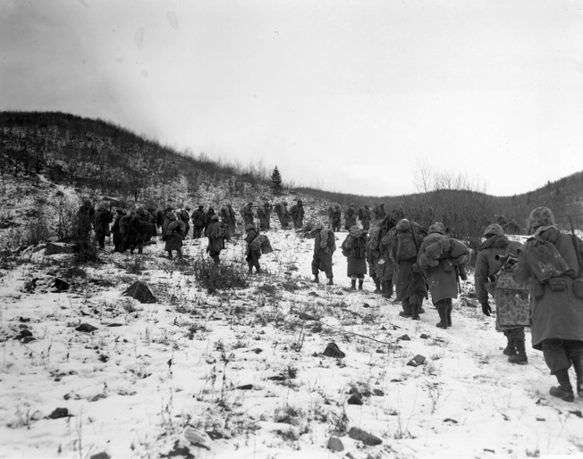 Marines trudge up a hill outside of Yudam-ni. These are probably the men of the 7th Marines moving in relief of one of the embattled perimeter companies.