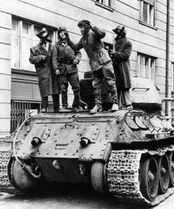 Soviet tankers are forced at gunpoint to disable their vehicle. The freedom fighters disabled the tanks by throwing stones and steel bars into their wheel treads.