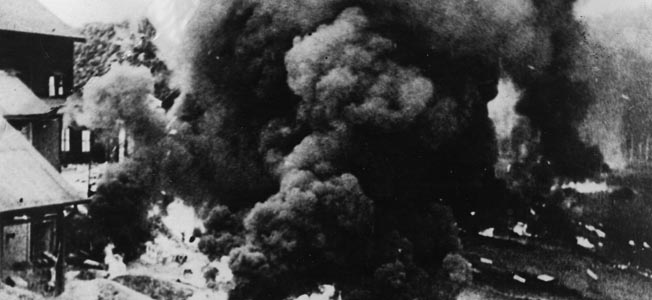 Clouds of pungent smoke pour from a Malayan rubber factory after being set afire by retreating British forces in order to prevent Japanese access to rubber reserves after the fall of Malaya in early 1942.