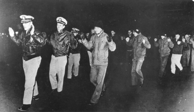 Bucher and his crew are forced to reenact their surrender two weeks after the North Korean sneak attack.