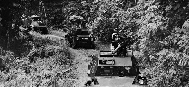 A Malayan government  convoy, led by a Ferret  armored car, moves warily  through the jungle in search  of insurgents.