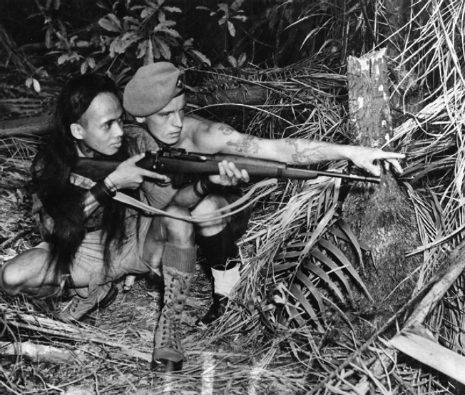 A British soldier trains a Malayan guide in the use of modern firearms.