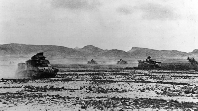 American M-3 Lee tanks, with hull-mounted 75mm cannons and 37mm turret-mounted guns, raise clouds of dust in the Tunisian desert.