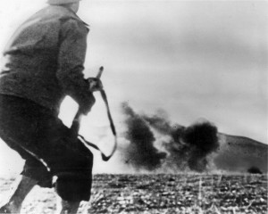Blast from a German bomb rattles this GI as he moves into position at Kasserine Pass.