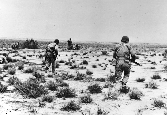 U.S. soldiers, weapons at the ready, advance warily toward German positions across the rock-strewn desert.