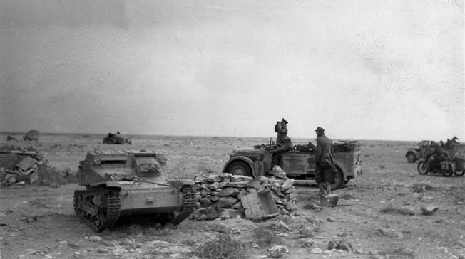 Field Marshal Erwin Rommel surveys the battle near the wreckage of a British Bren gun carrier.