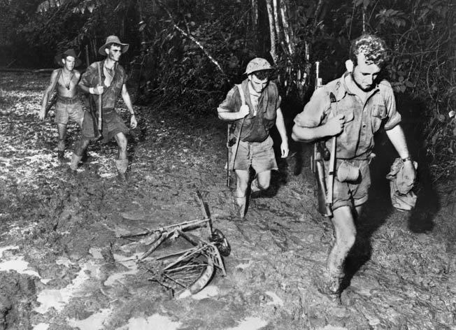 Mired in mud up to their ankles, Australian soldiers slog toward Buna along the Kokoda Trail in this photo from November 1942.