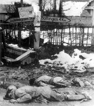 Dead American soldiers at a crossroads in Hinsfeld, Belgium. The soldier in the foreground has been stripped of his boots.