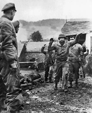 Americans surrender to the Germans. Isolated American infantry units received orders to hold their ground to allow time for reinforcements to reach the battlefront.