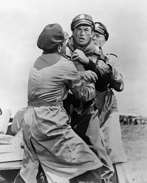 Brigadier General Savage (Gregory Peck) is restrained by Colonel Keith Davenport (Gary Merrill) and Major Stovall (Dean Jagger)