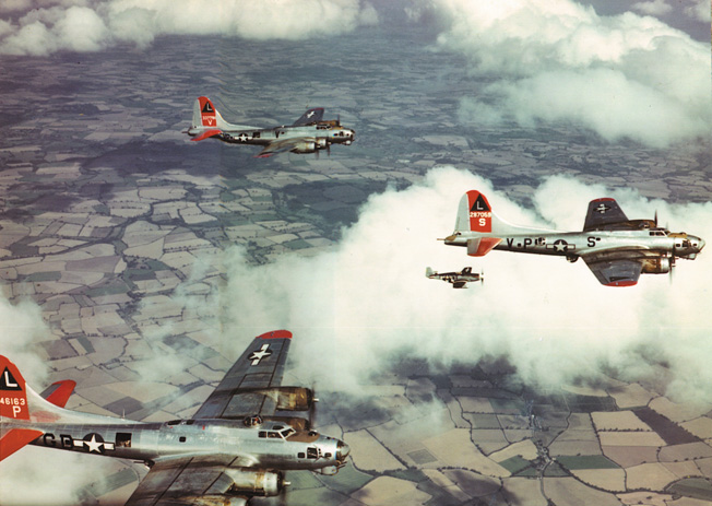 B-17s of the 8th Air Force, accompanied by fighters, cruise over England.