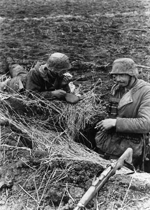 During the lull in the fighting on the steppes of Russia, a pair of German soldiers smoke a cigarette and eat a quick meal at their somewhat exposed position.