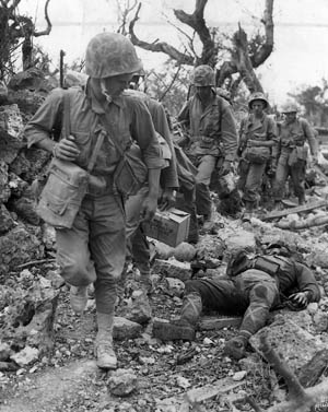 A line of Marines passes the body of a dead Japanese soldier, May 24, 1945. The tenacious defenders preferred death over dishonor.