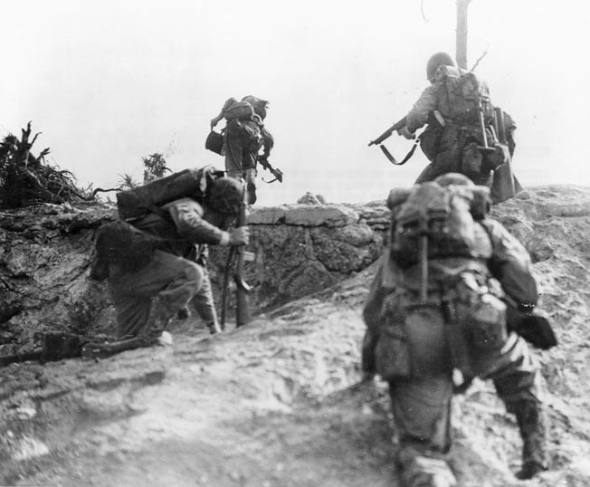 Summoning all their courage, Marines make an uphill assault against the entrenched enemy. A Marine (at left) carries a radio and another a spool of wire