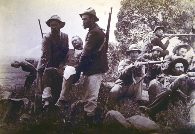 A badly wounded Boer is carried out of danger as his comrades keep watch with their Mausers.