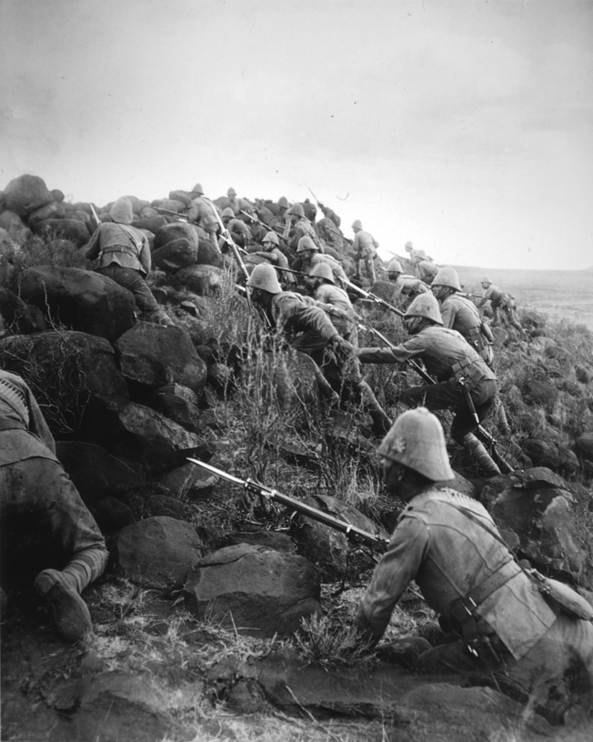 Carefully keeping their heads down, Canadian soldiers storm an outlying Kopje, or small hill, in front of the main Boer trench line at Paardeberg Drift