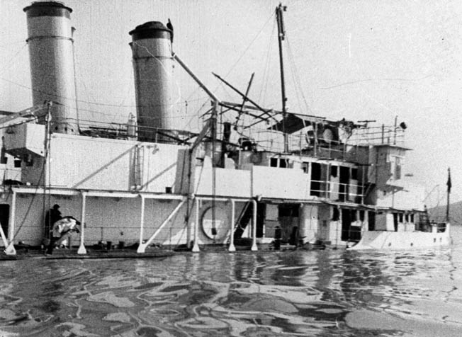 Its decks awash in the waters of the Yangtze River, the gunboat Panay lies helpless following the December 1937 attack by Japanese aircrafts unprovoked attack.
