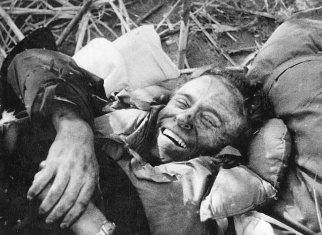 Although wounded, Hughes manages a smile for the cameraman after coming ashore.